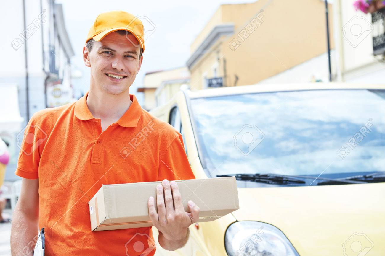 Smiling postal delivery courier man outdoors in front of cargo