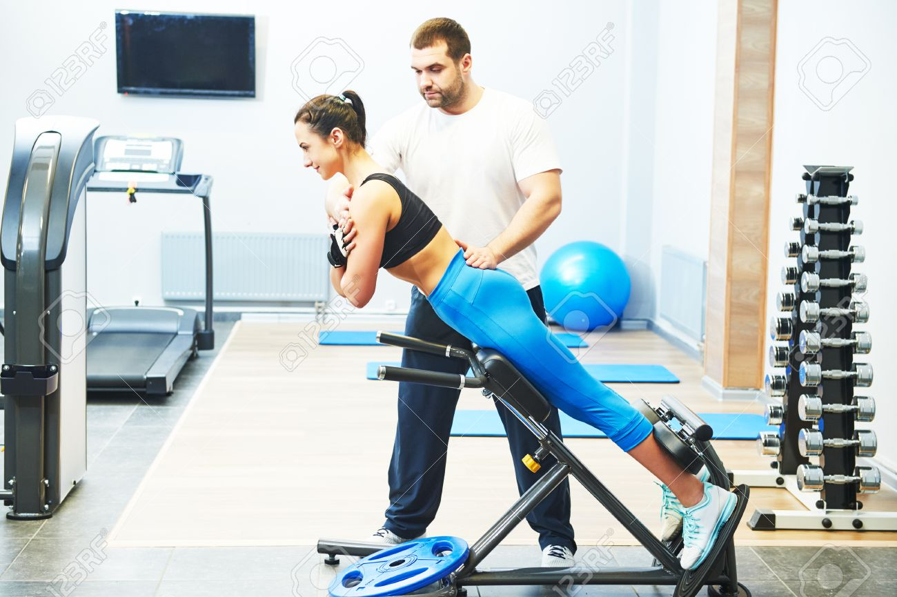 fitness and sport concept personal coach trainer helps w stock photo fitness and sport concept personal coach trainer helps w work out at a gym heavy weight