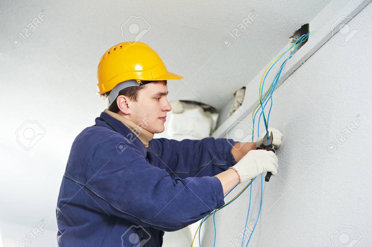Male electrician at work laying wiring cable on