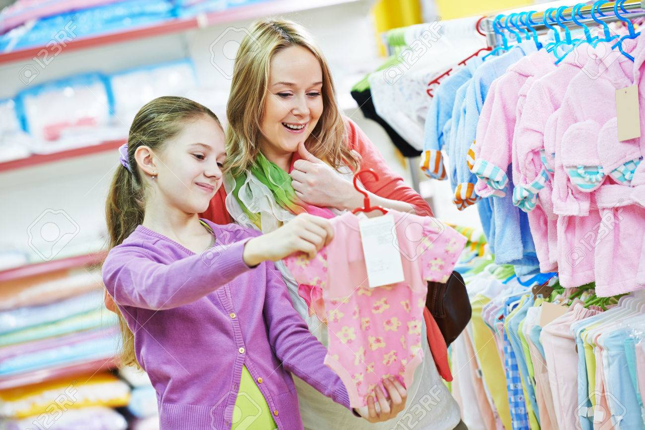 e531b45ac Pregnant Woman And Little Girl Choosing Newborn Baby Clothes.. Stock ...