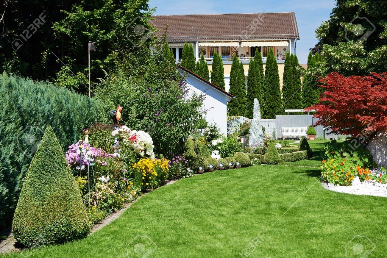 Diseño De Paisaje. Jardín Con Césped Verde Y Flores Cerca De Casa Foto De  Archivo
