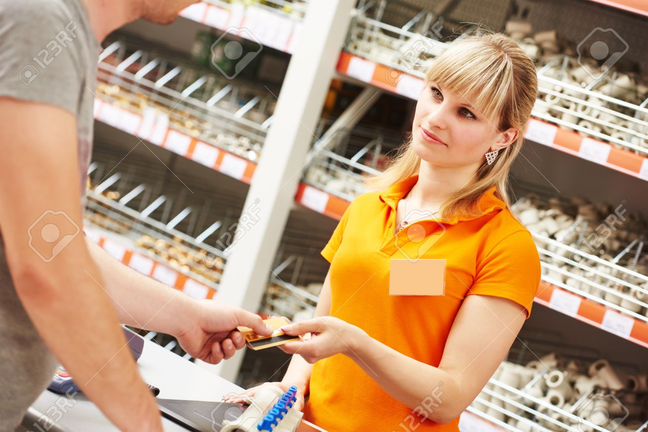 hardwarre seller or assistant cashier accepting credit card hardwarre seller or assistant cashier accepting credit card as payment for purchase stock photo