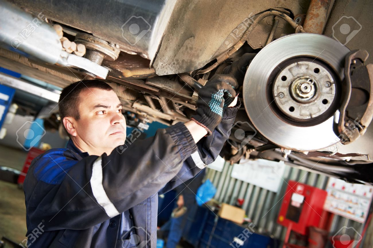 automobile mechanic inspecting car wheel brake disc and shoes