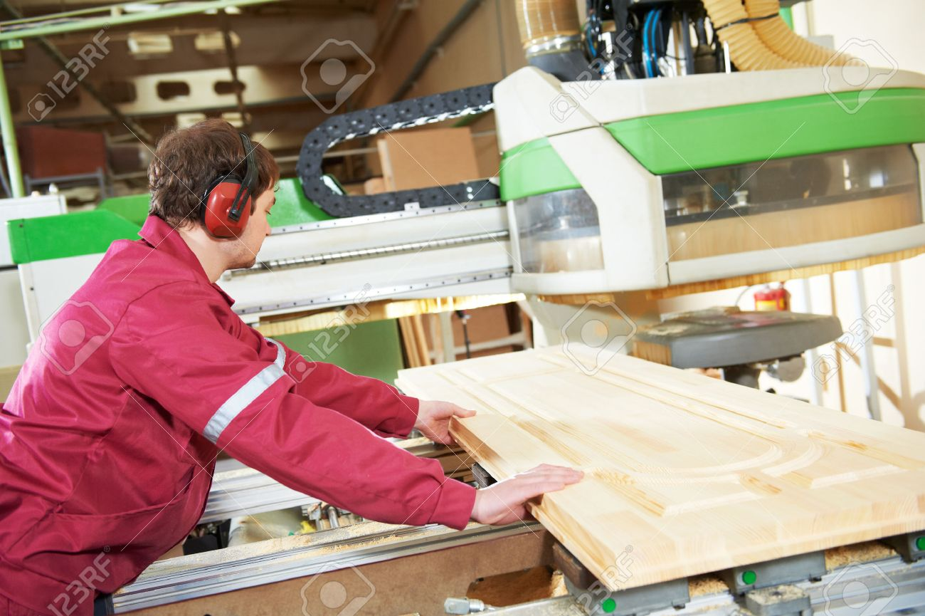 Good Industrial Carpenter Worker Operating Wood Cutting Machine During Wooden  Door Furniture Manufacturing Stock Photo   41781886