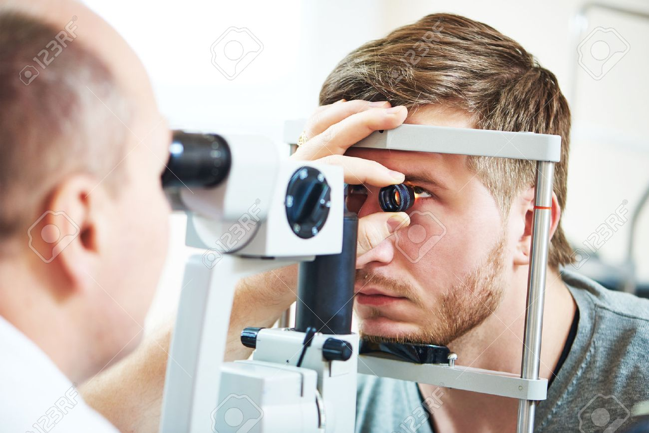Ophthalmology concept. Male patient under eye vision examination in eyesight ophthalmological correction clinic Standard-Bild - 58661683