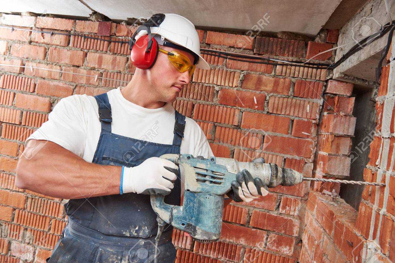 Builder worker with pneumatic hammer drill perforator equipment making hole in wall at construction site Standard-Bild - 58661700
