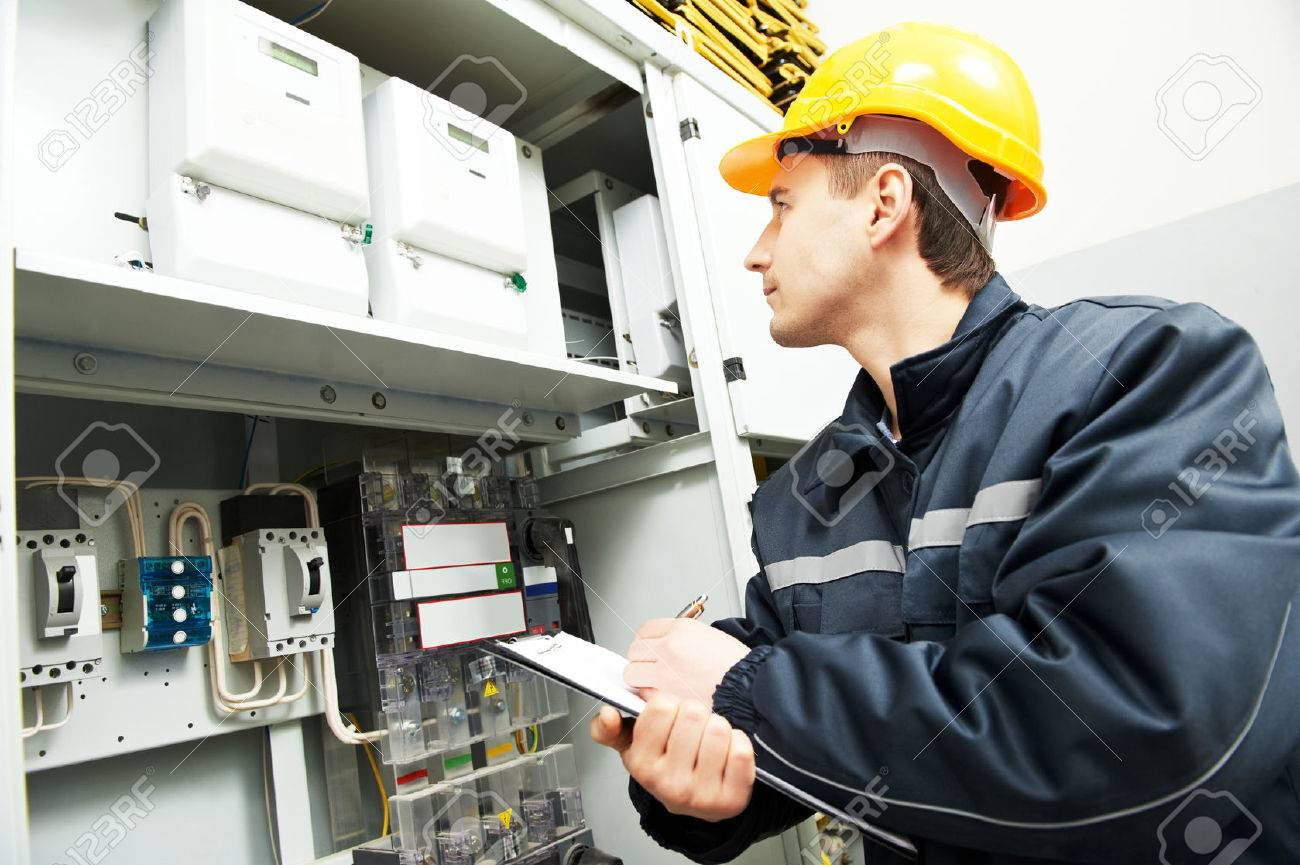 electrician builder engineer inspector checking data of equipment in fuse box Standard-Bild - 58661764