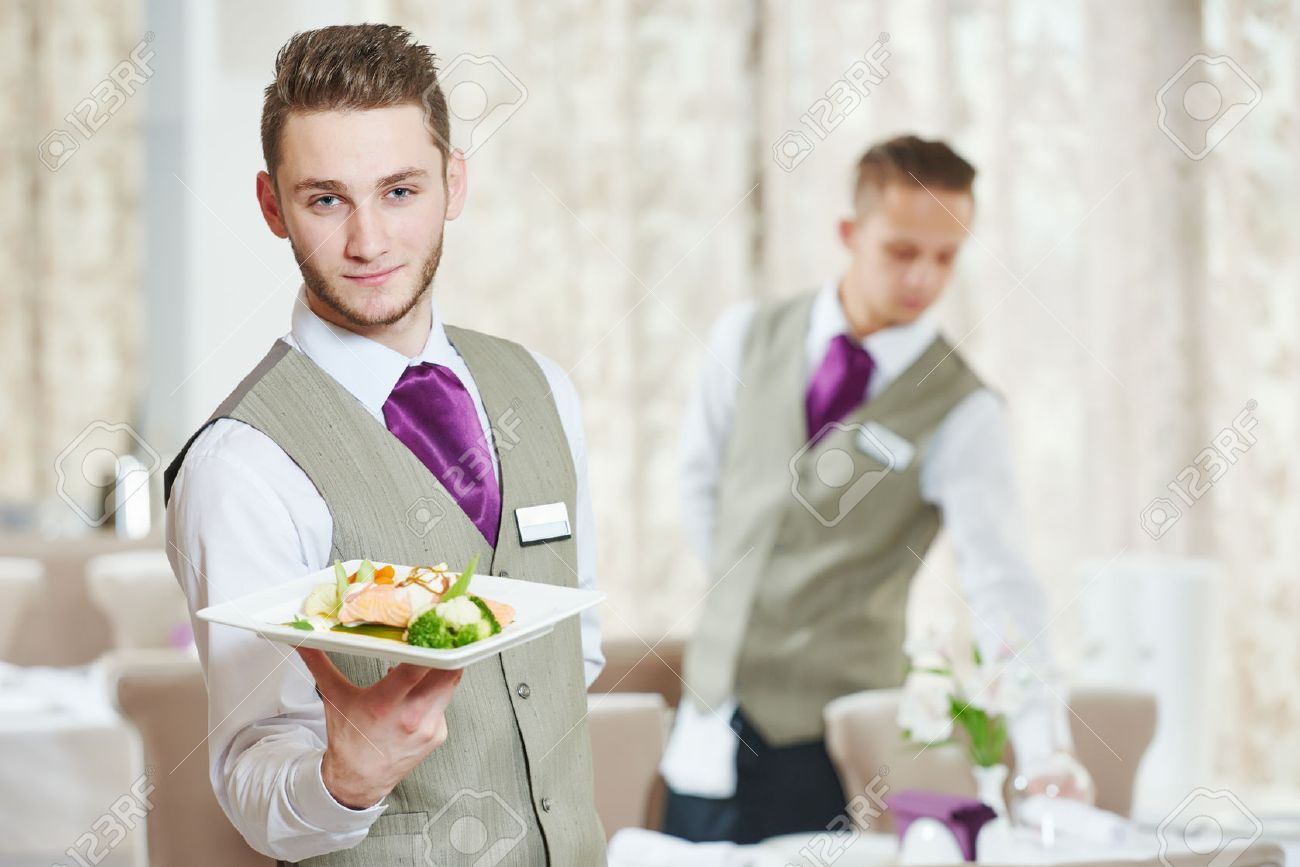 Waiter occupation. Young man with food on dishes servicing in restaurant - 48492426