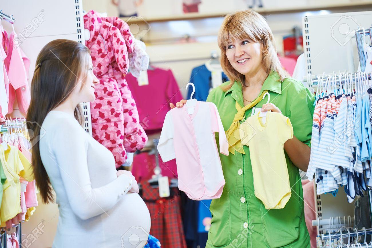 06596f2568f Comercial embarazo. Mujer vendedora de venta de ropa de recién nacidos a  joven mujer embarazada