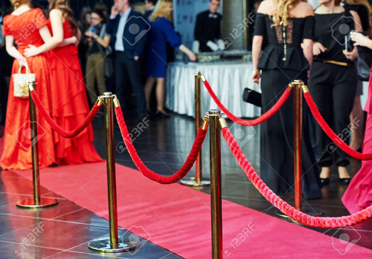 event party. red carpet entrance with golden stanchions and ropes. guests in the background - 50038038