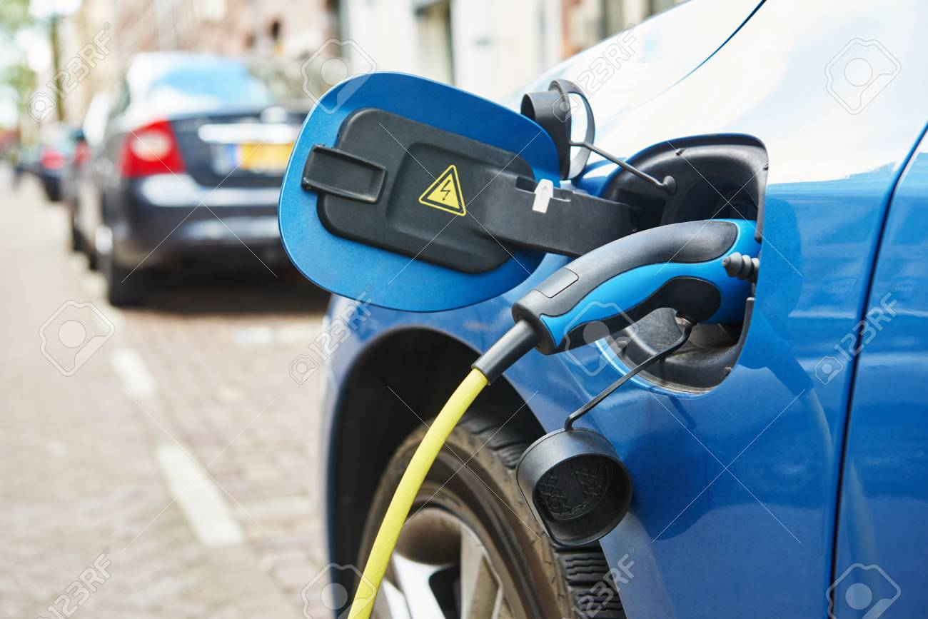 alternative eco energy fuel. Close up of the power supply plugged into an electric car during charging in Amsterdam - 50038053