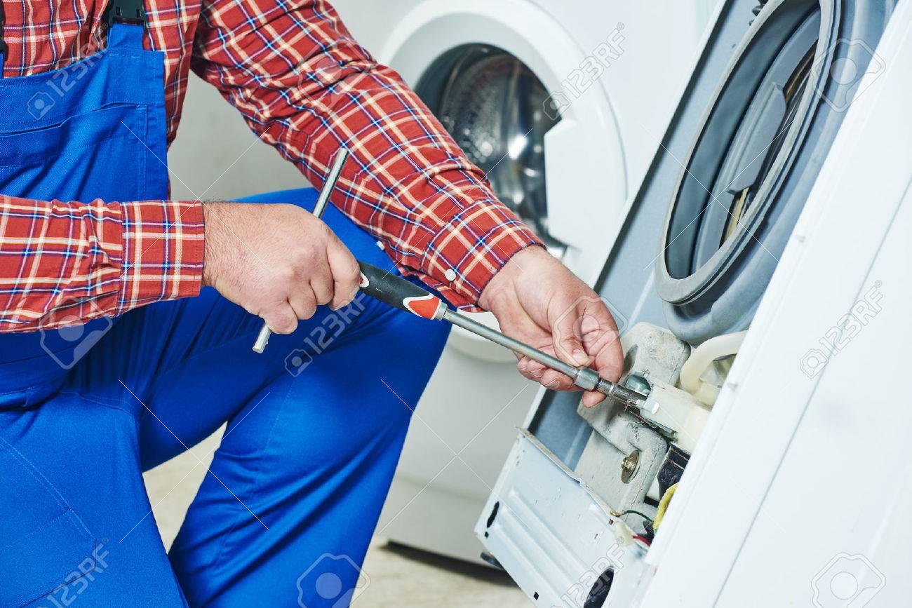 Washing machine repair. Repairer hands with screwdriver disassembling damaged unit for repair - 50038136
