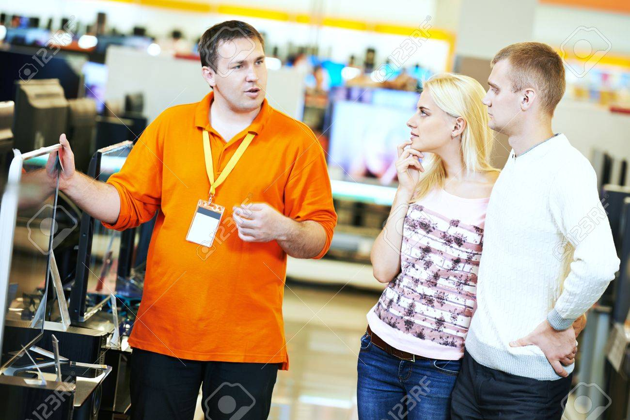 Young family choosing tv set with shop assistant in home appliance shopping mall supermarket - 50645389