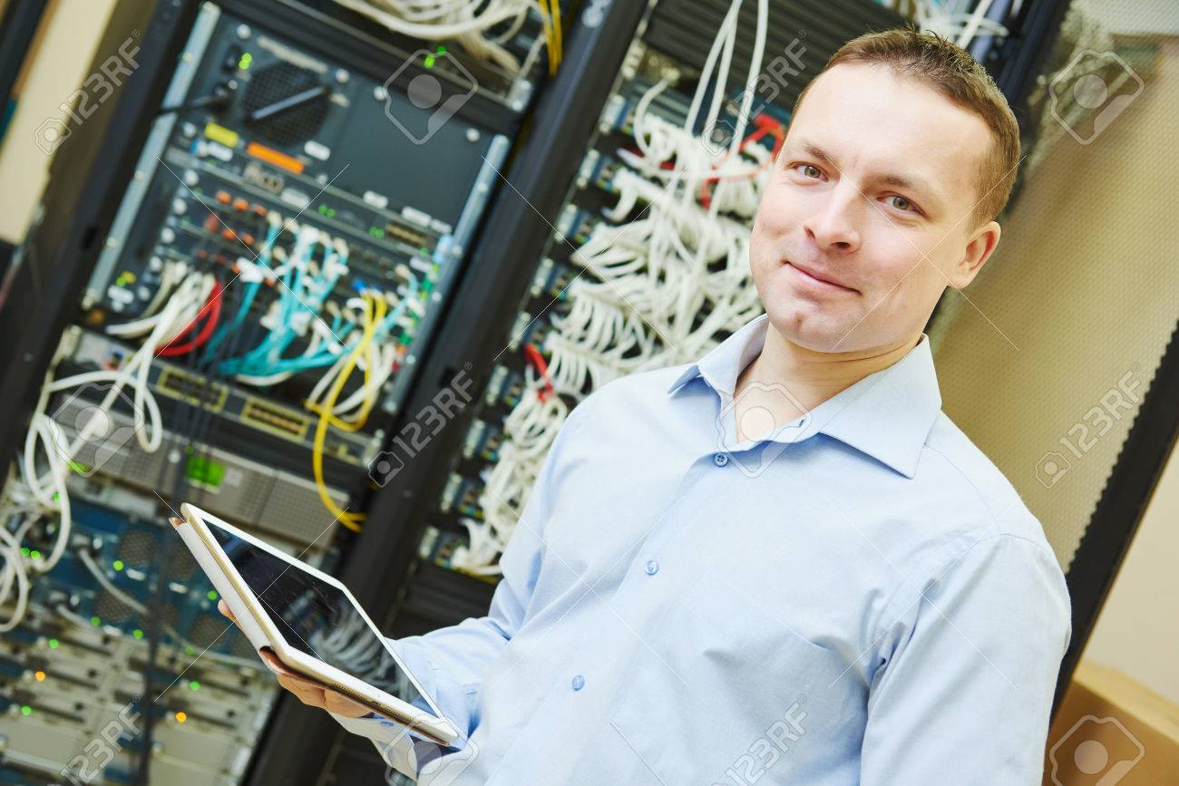 Networking service worker portrait. network engineer administrator with tablet computer checking server hardware equipment of data center Stock Photo - 52239904