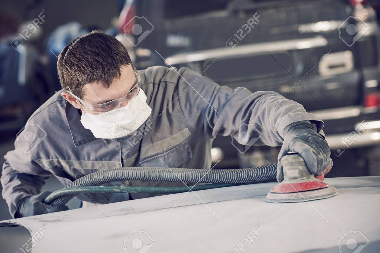 Auto body repairs. Repairman mechanic worker grinding automobile car bonnet by grinder in garage workshop. Toned Stock Photo - 55560517