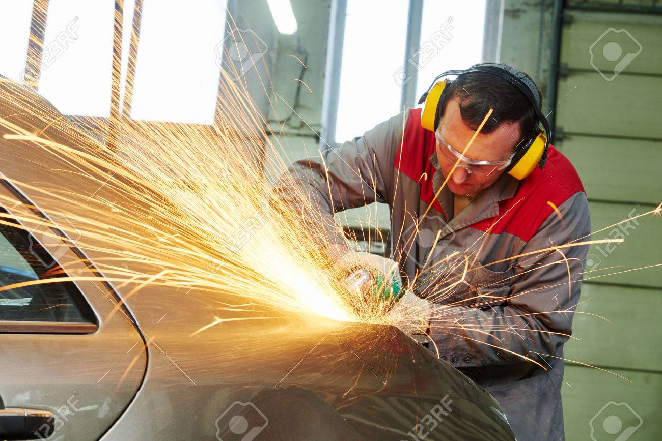 collision repairs service. auto repair mechanic grinding car body by grinder Stock Photo - 55560528