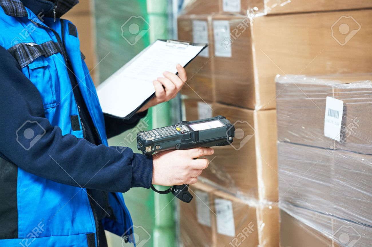 Male worker scanning package with barcode scanner in modern warehouse Stock Photo - 55593235
