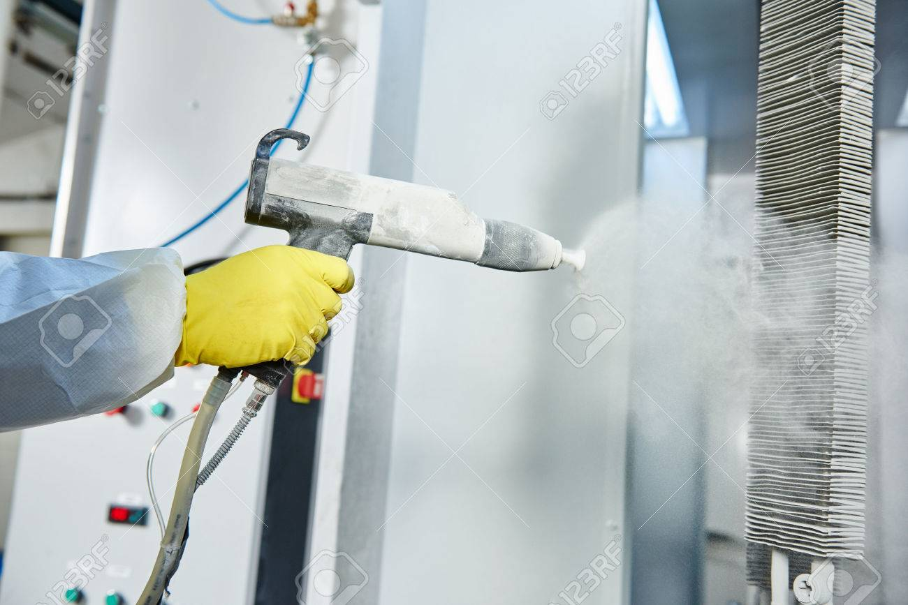 industrial metal coating. Worker man in protective suit with gas mask spraying powder to steel finished parts in painting chamber Standard-Bild - 56899688