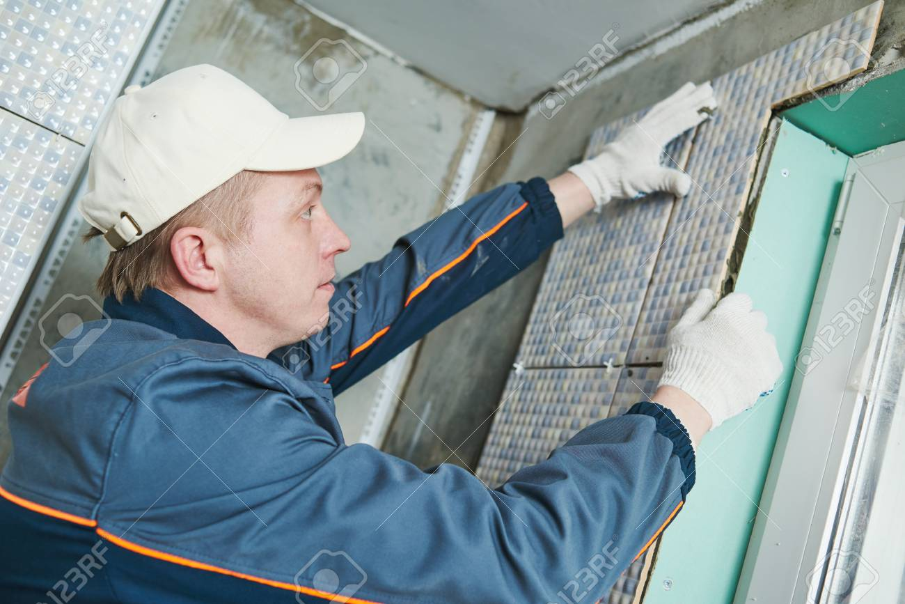 industrial tiler builder worker installing wall tile at repair renovation work - 56909311