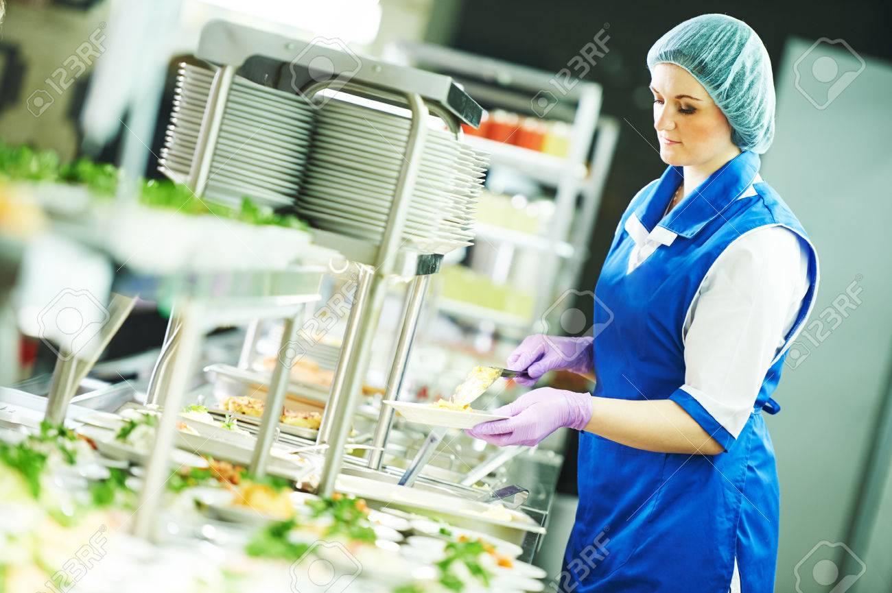 buffet female worker preparing and servicing food in cafeteria Standard-Bild - 57001010