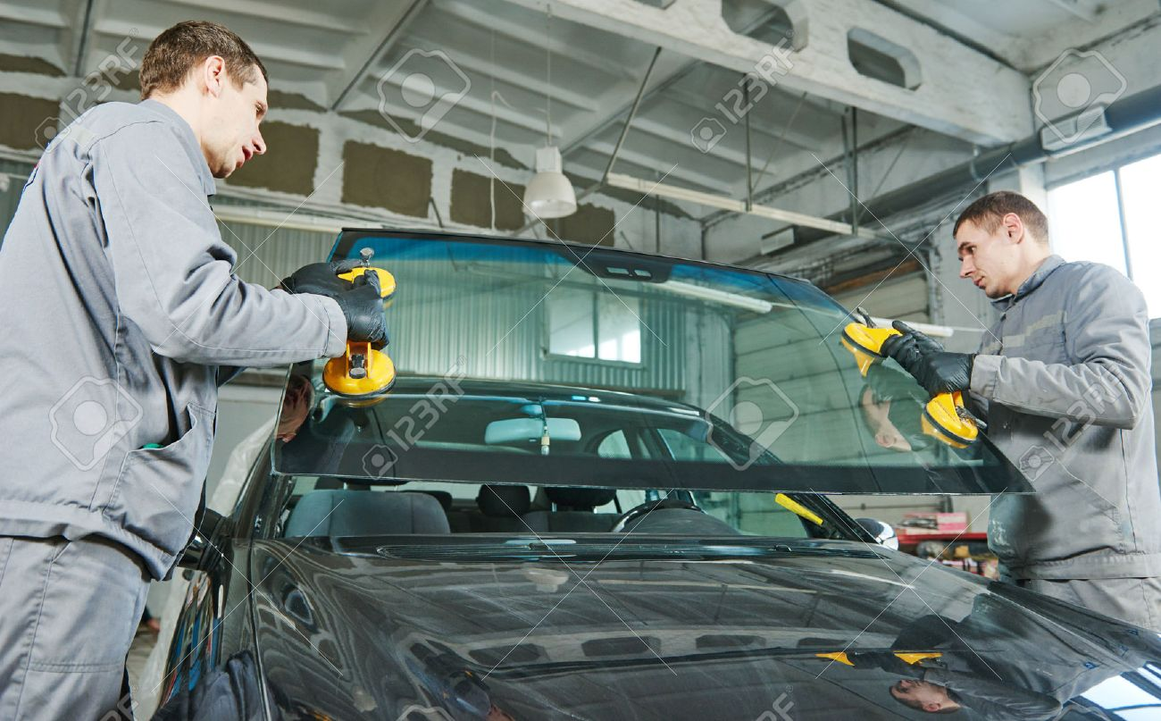 Glazier repairman mechanic worker replaces windshield or windscreen on a car in automobile workshop garage Standard-Bild - 60840683