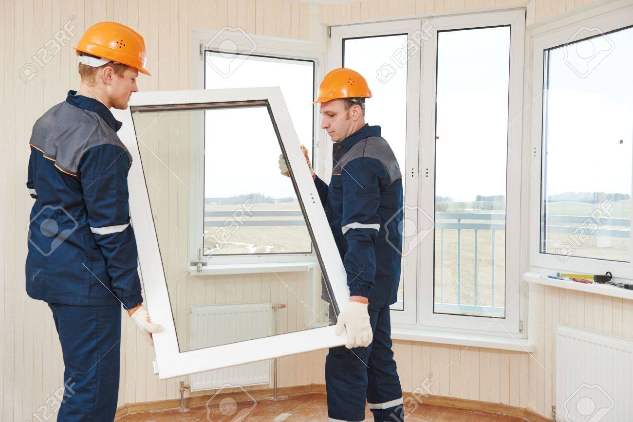 two windows installation workers installing double-glass pane - 60846287
