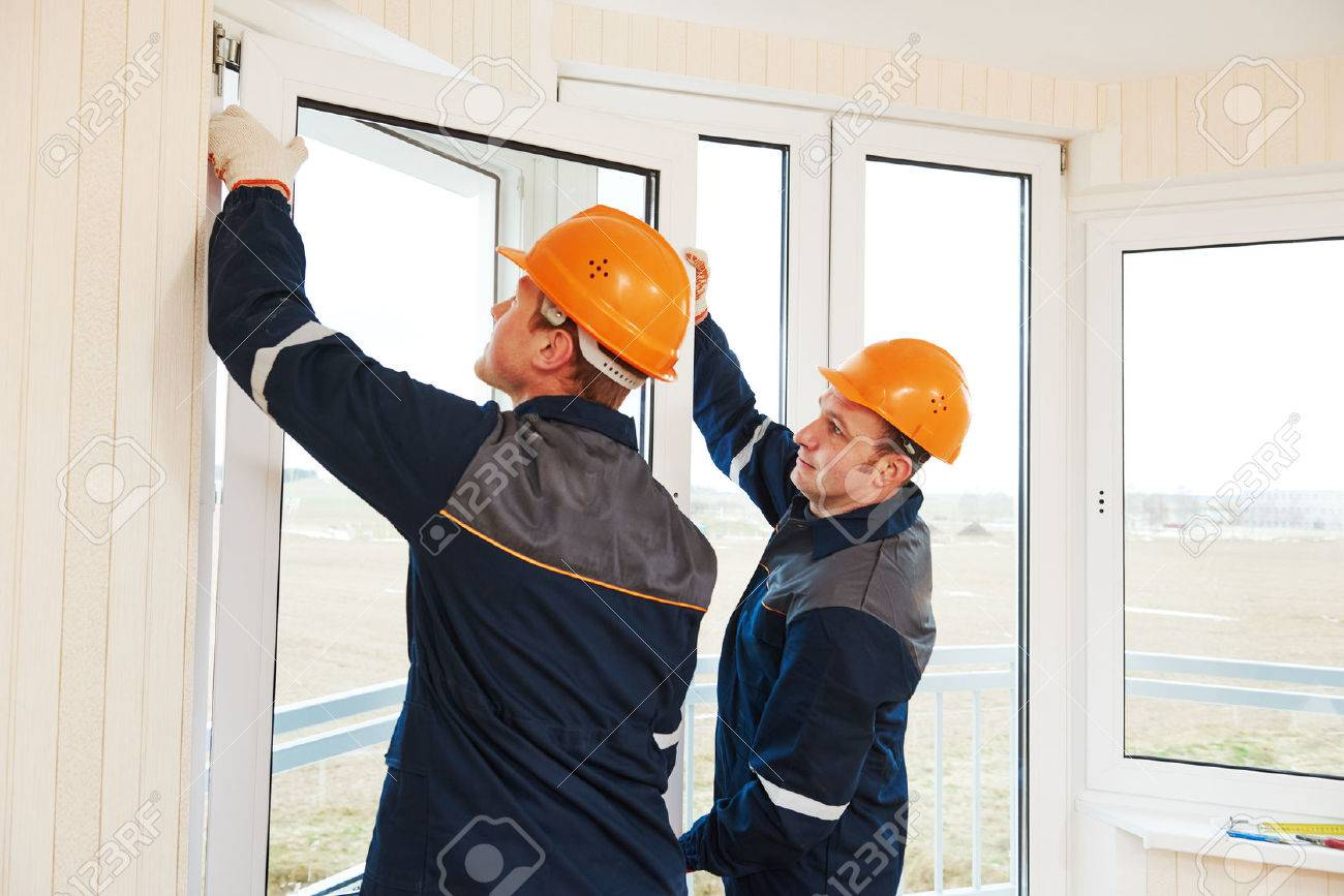 two windows installation workers installing double-glass pane - 60846286