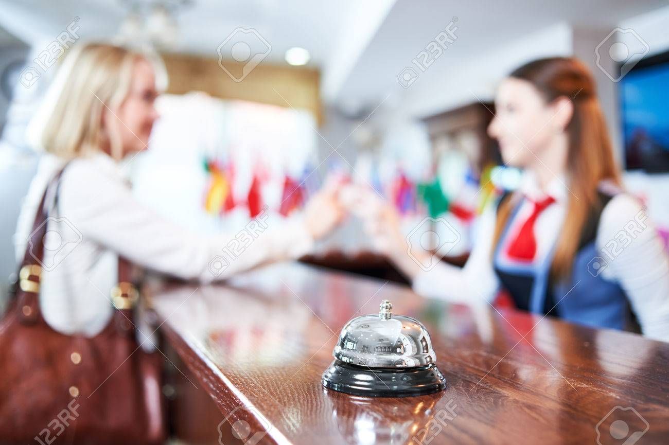 Hotel service. Female receptionist handing over electronic room key card to a client at the reception desk Standard-Bild - 60846405