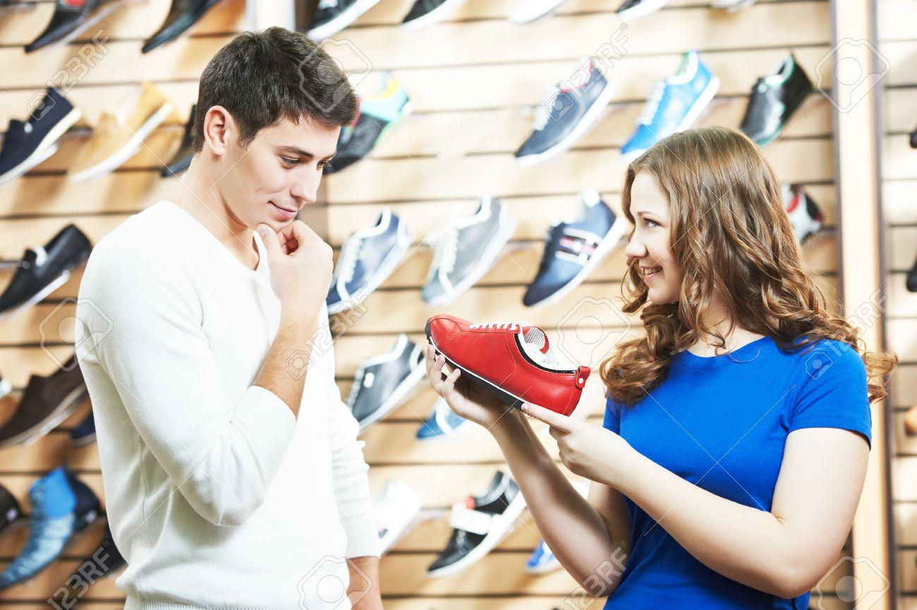 249d91afeacebe Standard-Bild - Verkäufer Assistentin Schuhe junger Mann während Schuhe  einkaufen im Schuhgeschäft demonstrieren