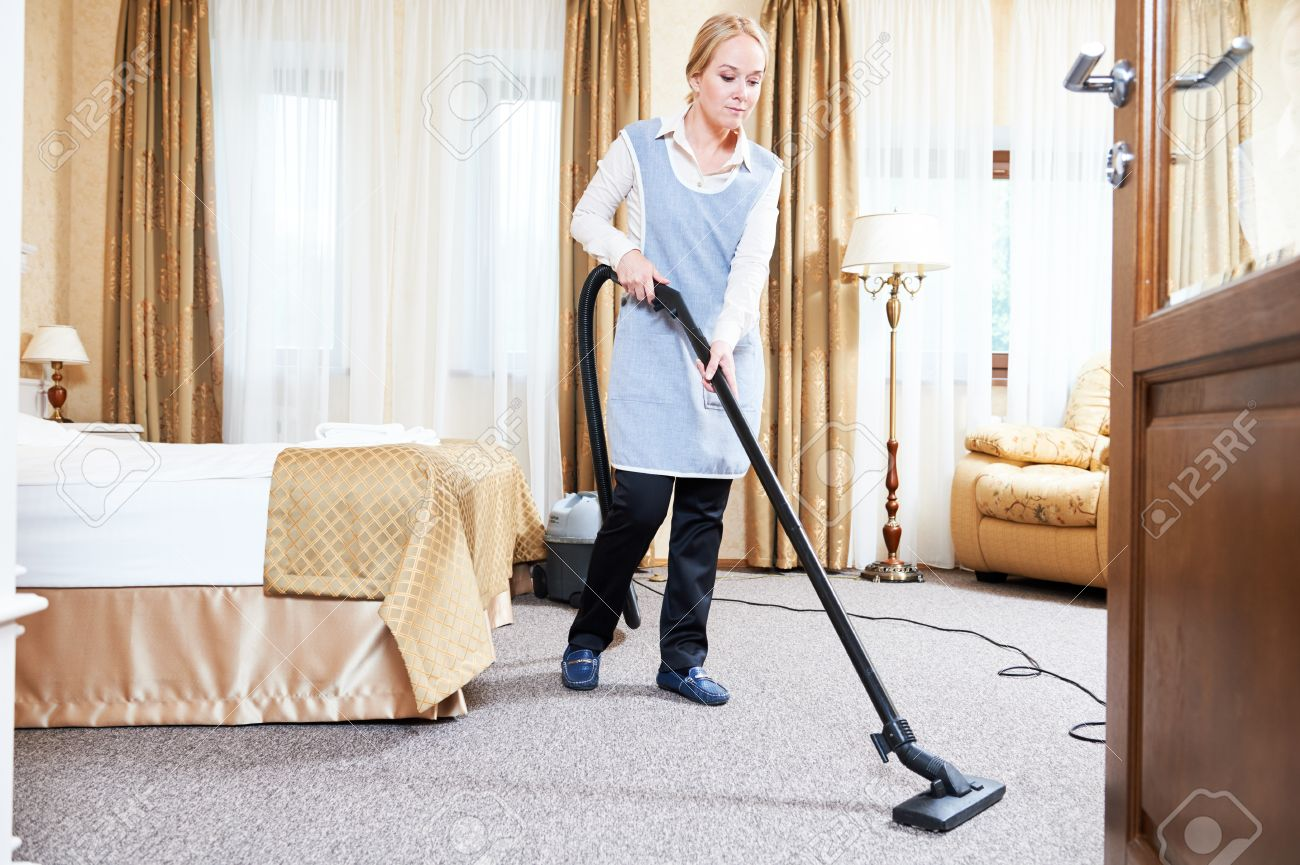 Hotel Service. Female Housekeeping Maid Worker With Vacuum Cleaner In Room  Apartment Stock Photo