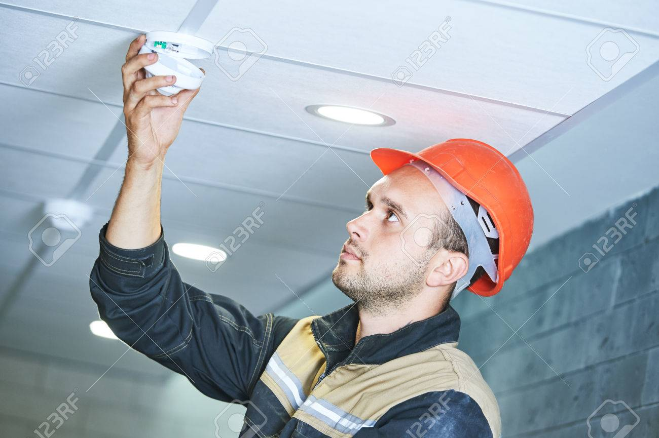 construction worker installing smoke detector alarm on the ceiling - 62299643