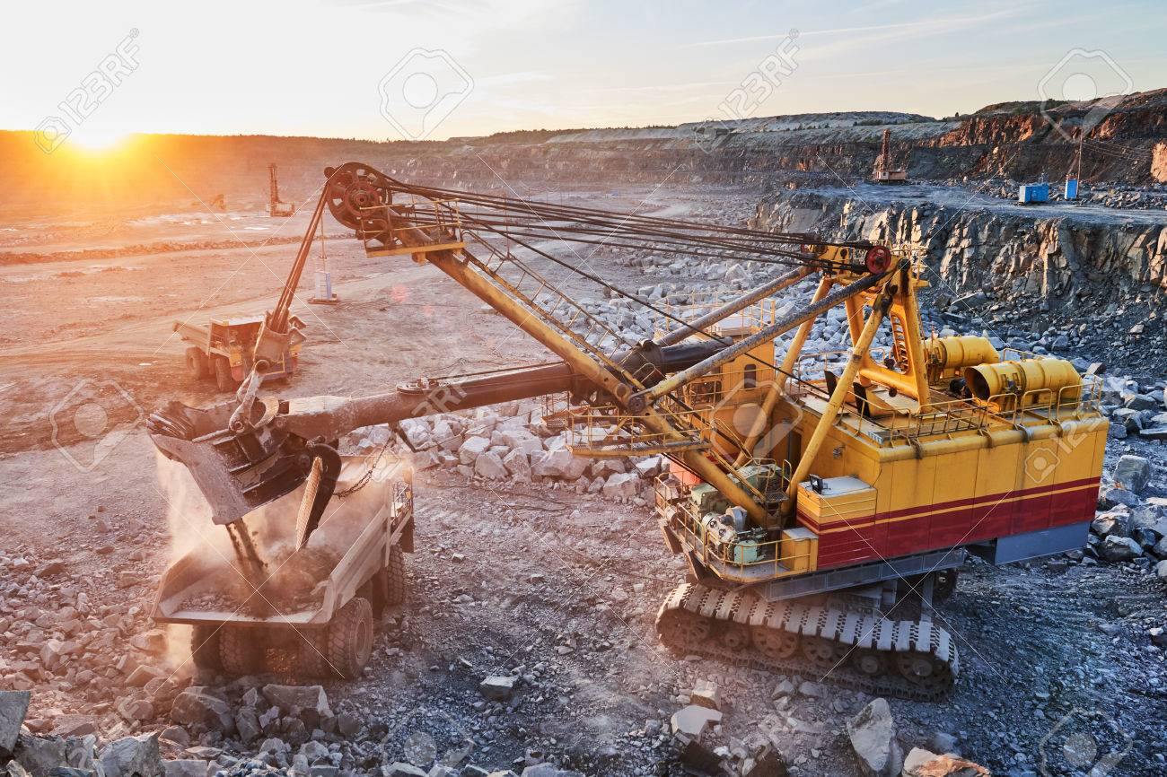Mining industry. Heavy excavator loading granite rock or iron ore into the huge dump truck at opencast quarry. Sunset Stock Photo - 64987198