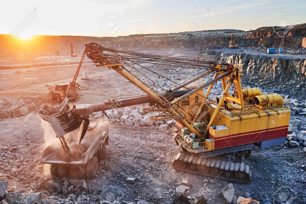 Mining industry. Heavy excavator loading granite rock or iron ore into the huge dump truck at opencast quarry. Sunset Standard-Bild - 64987198