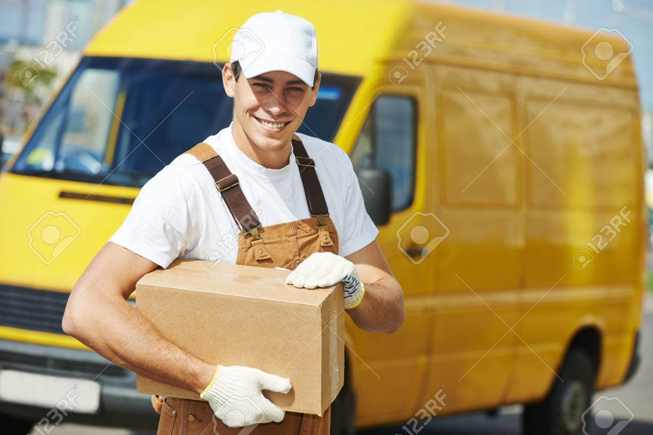 Smiling Young Male Postal Delivery Courier Man In Front Of