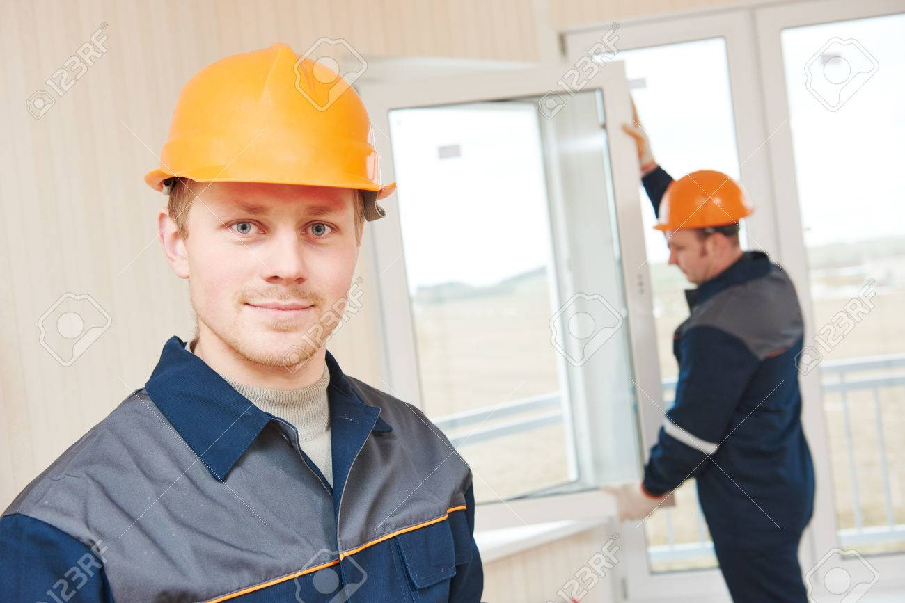 two window installation workers installing double-glass pane Stock Photo - 69686984