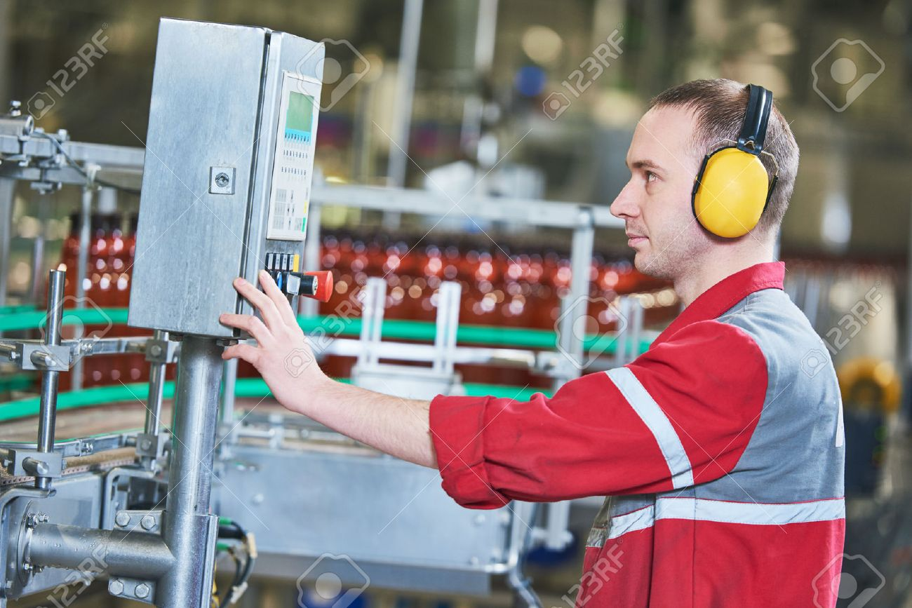food and drink production industry. Factory worker operating conveyor for plastic bottles with beer or carbonated beverage moving Stock Photo - 67104031