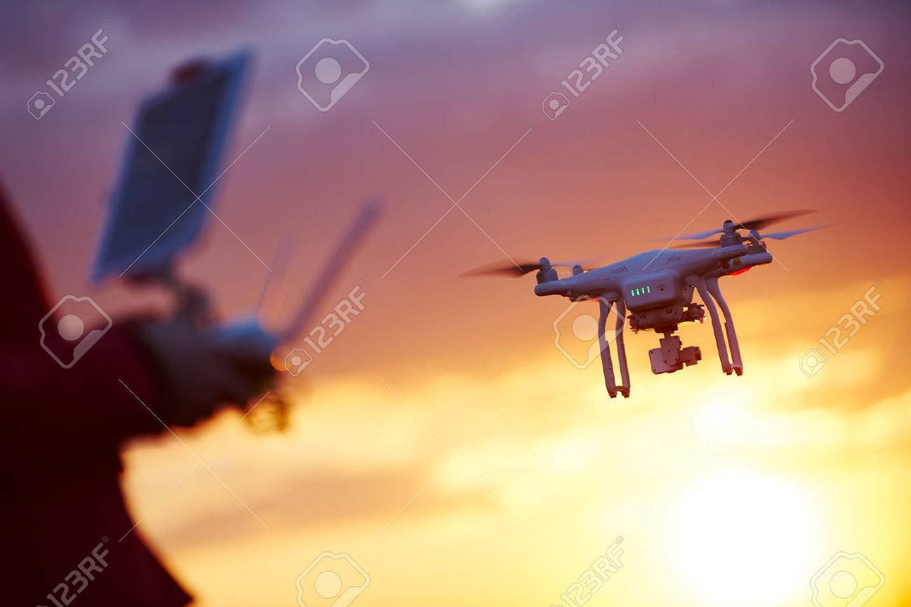 piloting flying copter drone at sunset - 68464330