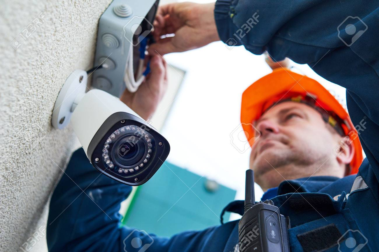 Technician worker installing video surveillance camera on wall Standard-Bild - 70443943