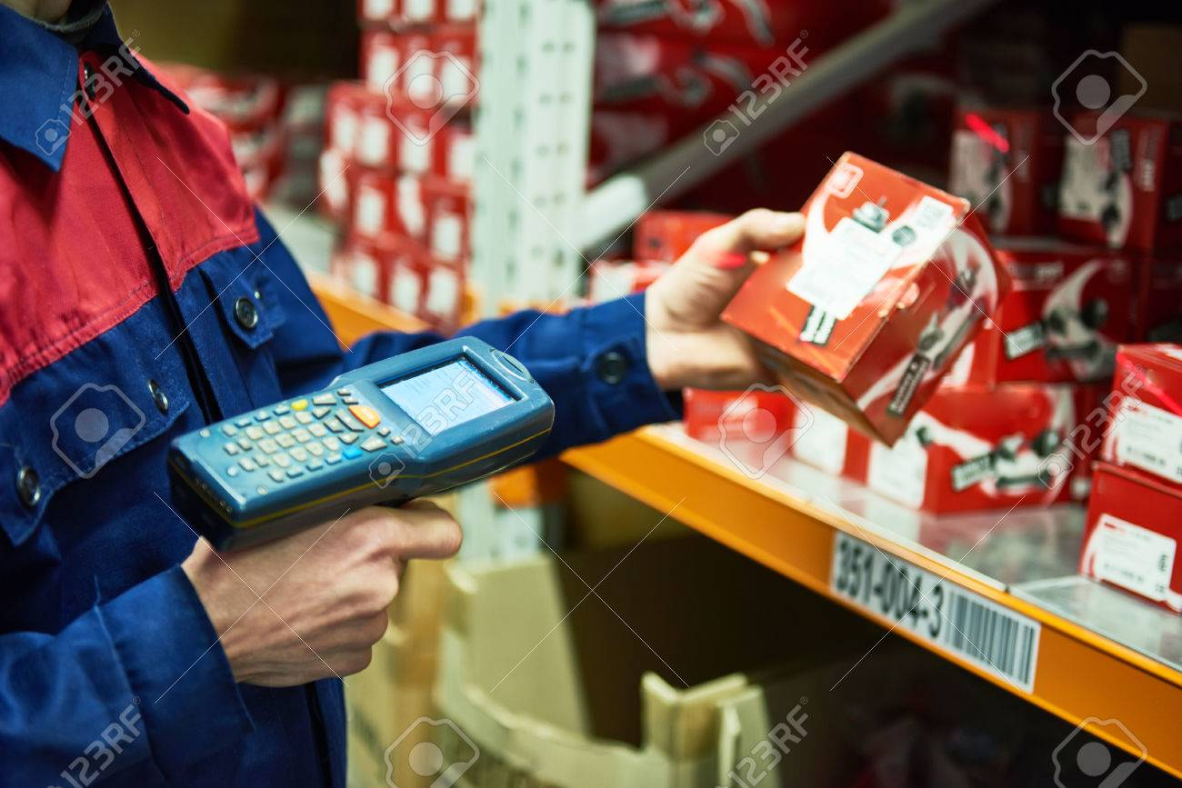 warehouse worker scanning automobile spare part with laser barcode scanner - 77052087