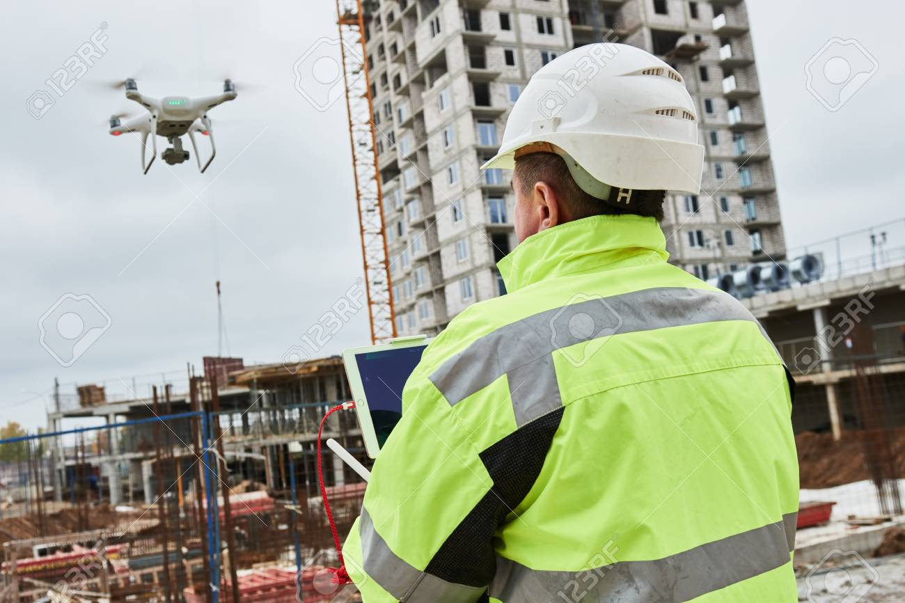 Drone operated by construction worker on building site - 88540595