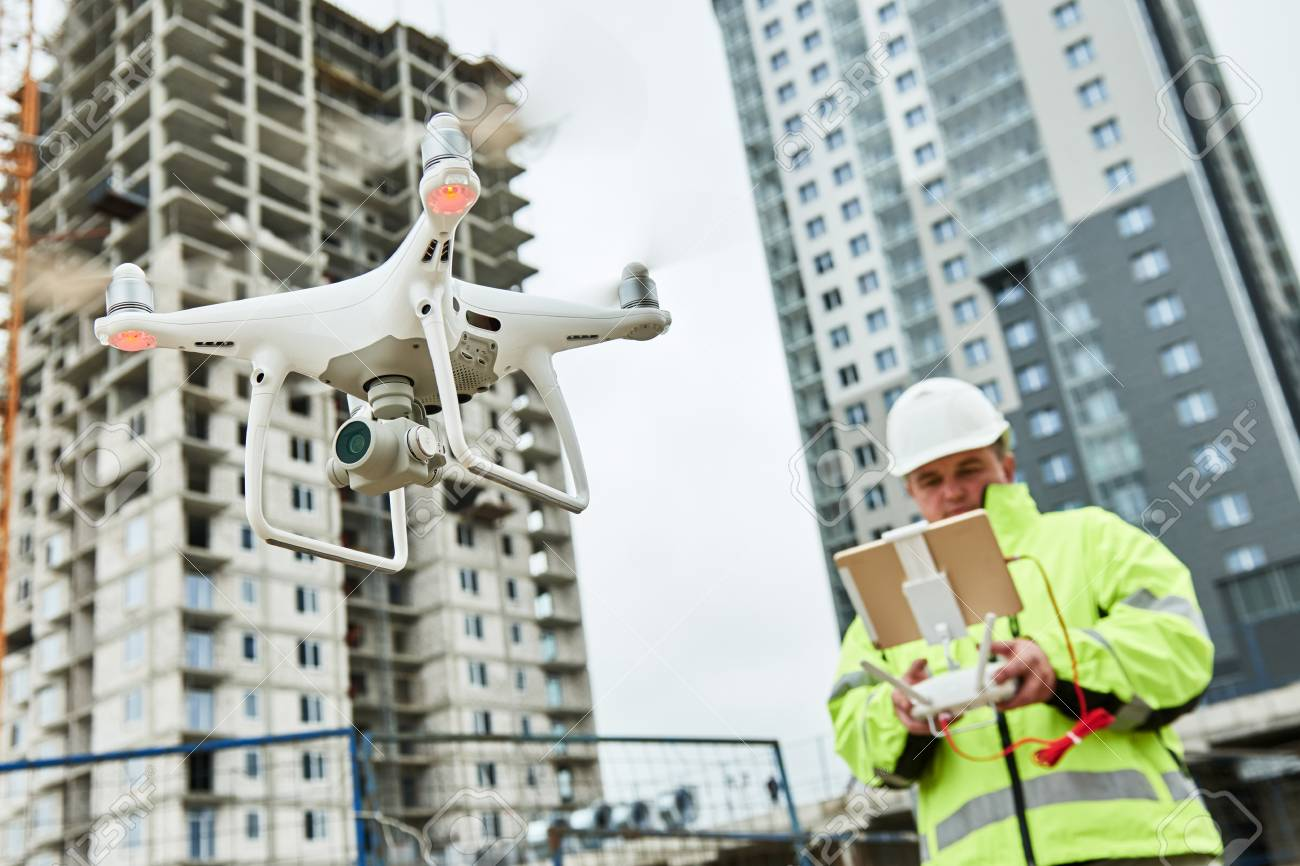 Drone operated by construction worker on building site - 88540671