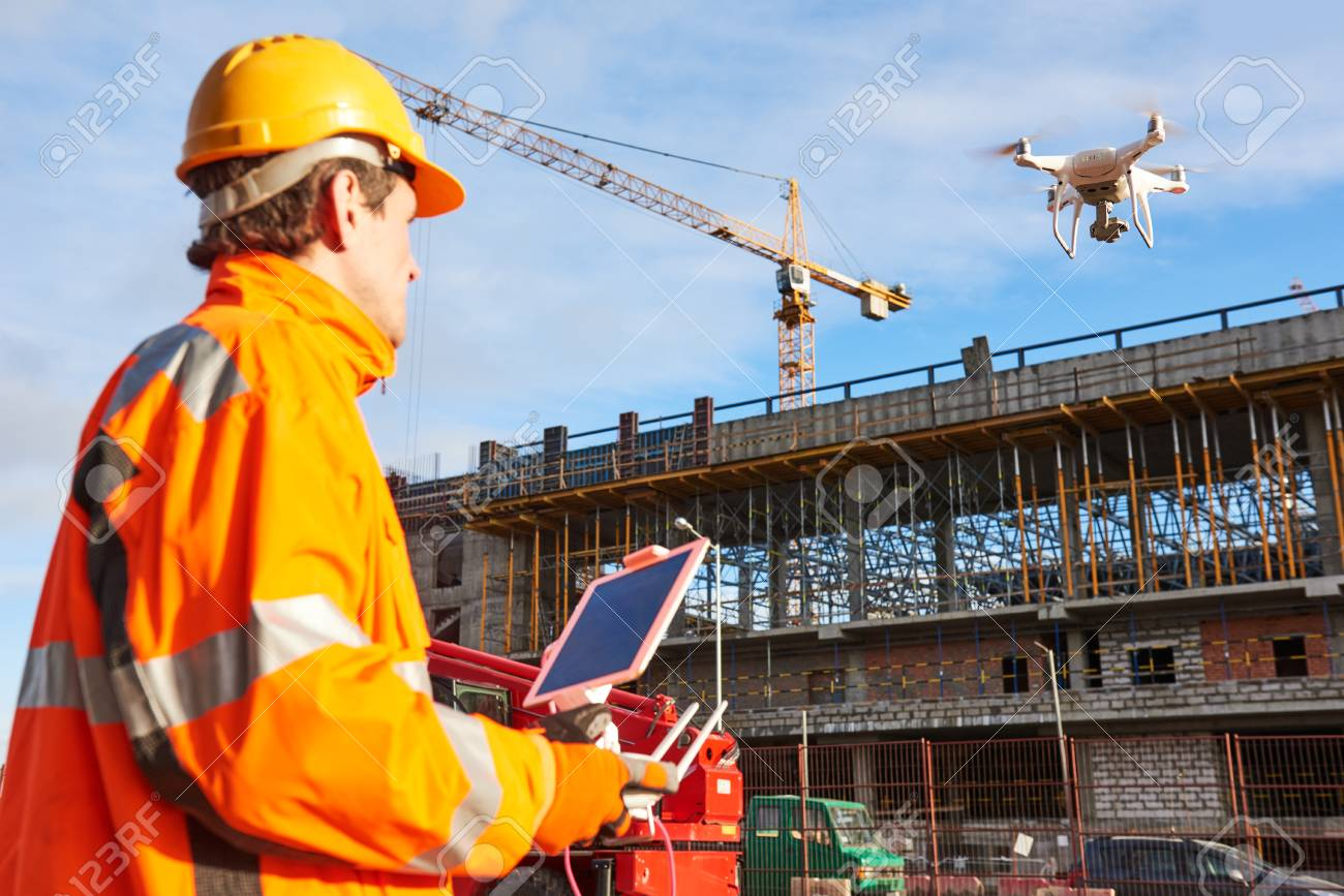 Drone operated by construction worker on building site - 92134511
