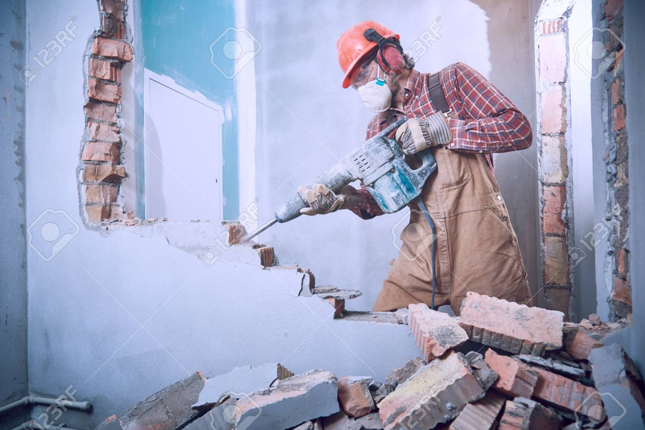 worker with demolition hammer breaking interior wall - 92106897