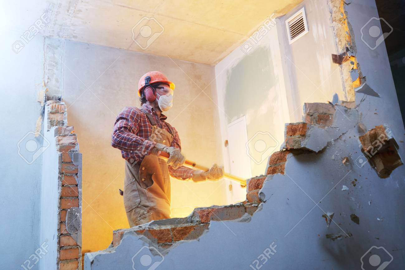 worker with sledgehammer at indoor wall destroying - 92406800