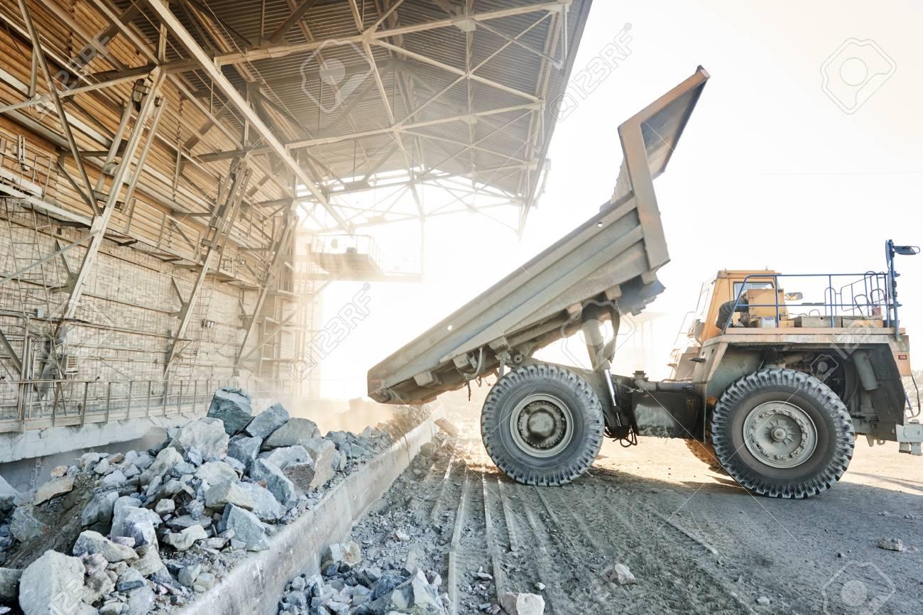 Huge Dump Truck Unloading Granite Rock Or Iron Ore Stock Photo