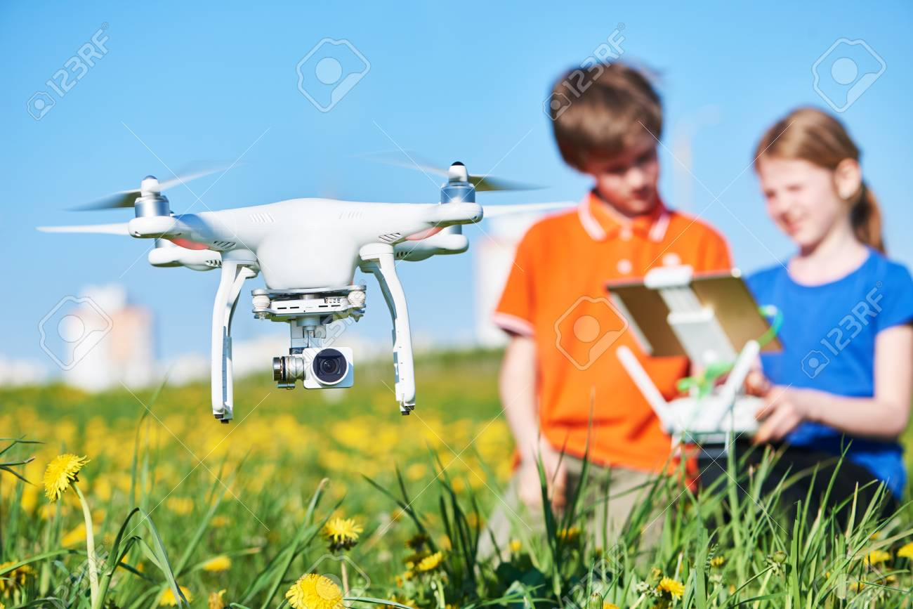children operating of flying drone at sunset - 93307049