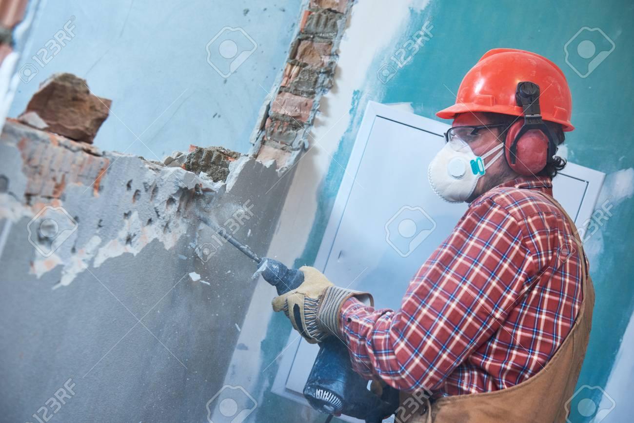 worker with demolition hammer breaking interior wall - 97510567