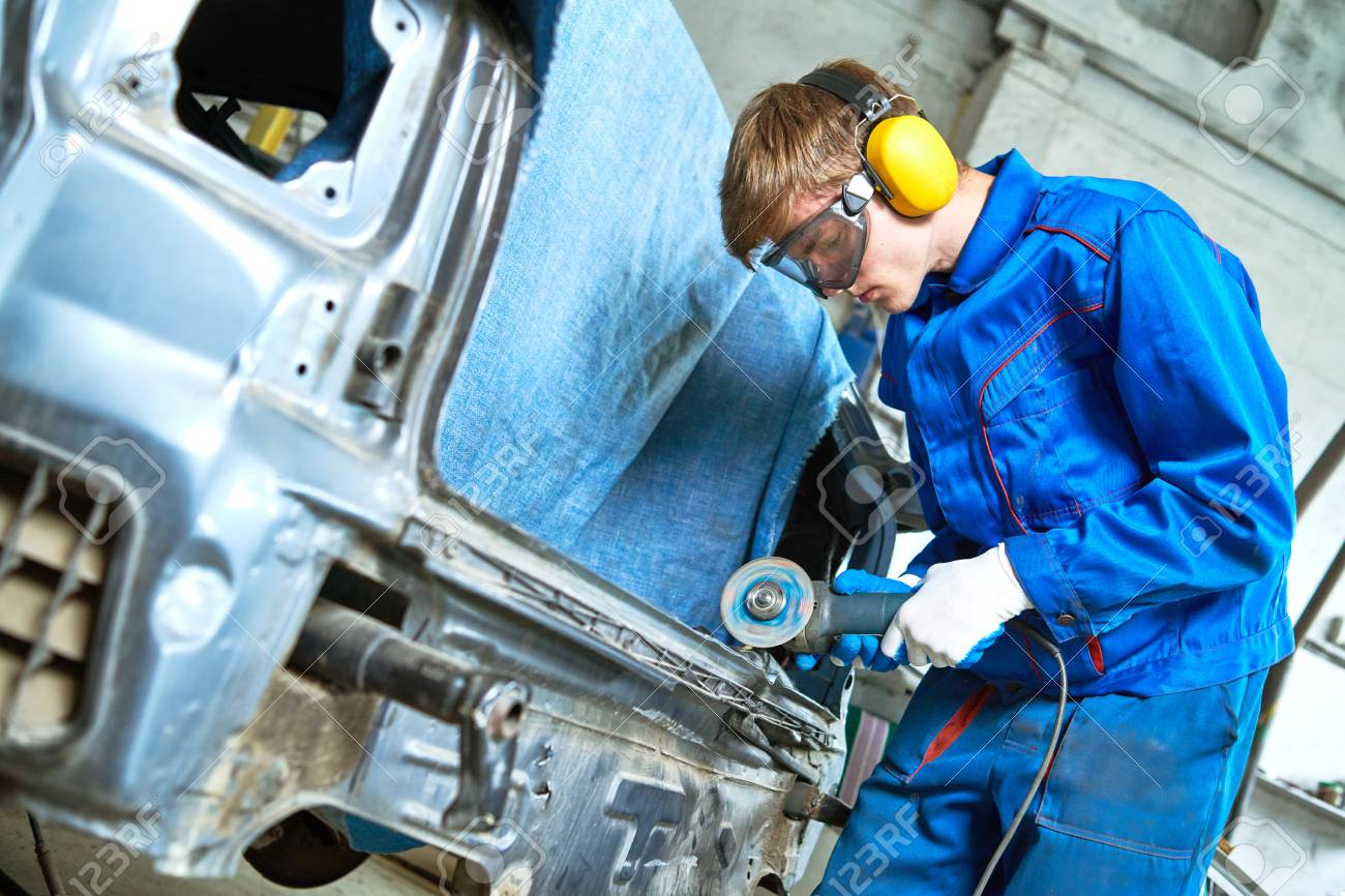 collision repairs service. mechanic grinding car body by grinder - 107412807