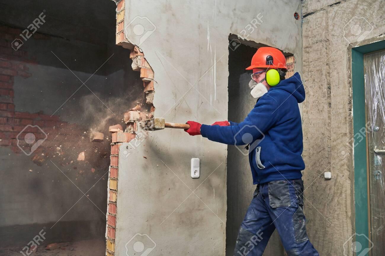 demolition work and rearrangement. worker with sledgehammer destroying wall - 118735881