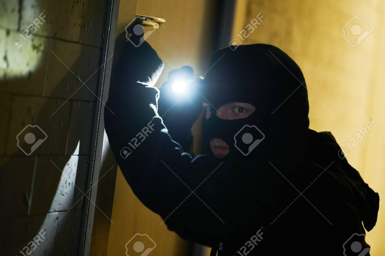 Burglar thief in mask. break-in of an apartment. - 118736084